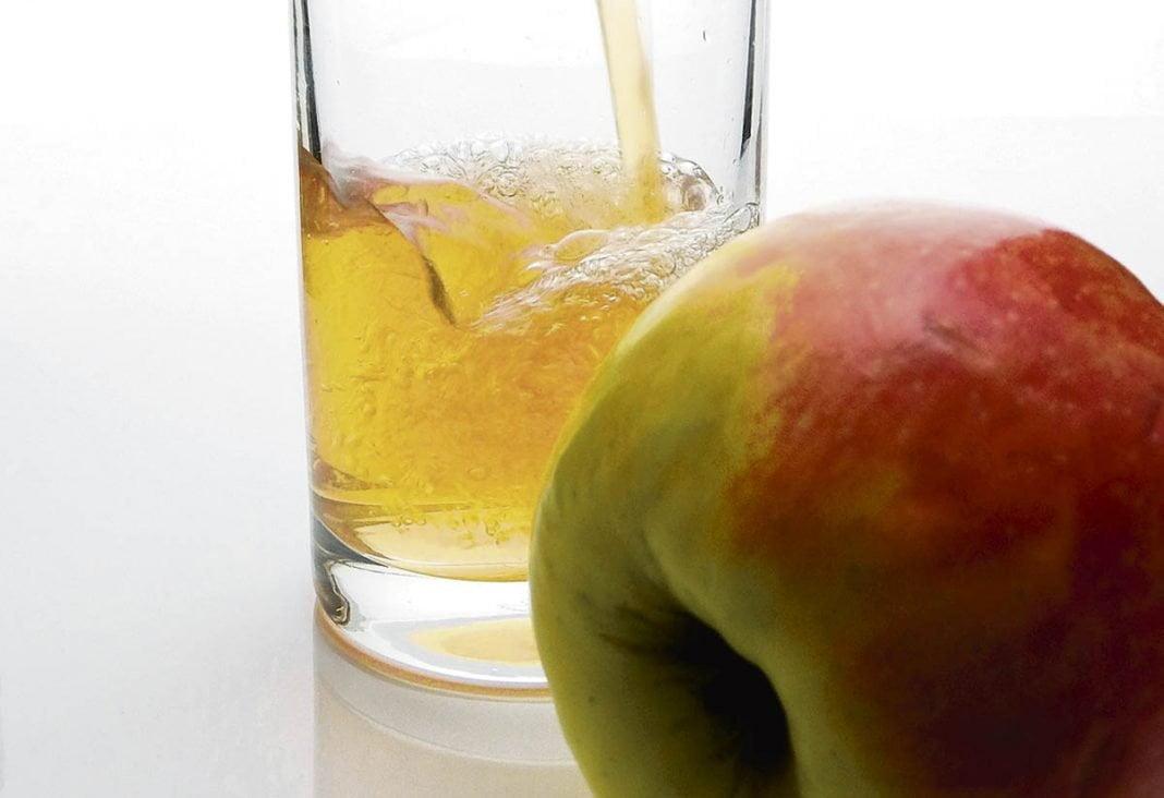 Verre de cidre en train de se faire verser derrière une pomme