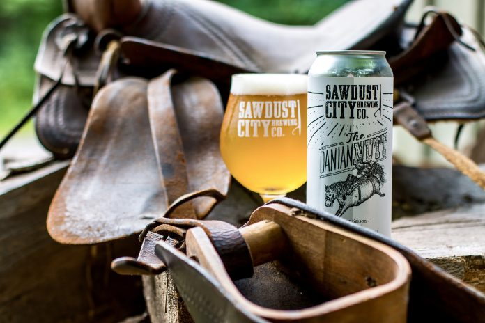 Photo d'une verre et d'un cannette de la 1ere collaboration : « The Danian Nutt » avec Sawdust City Brewing Co. devant une selle