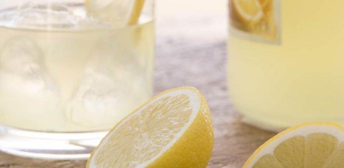 Liqueur de citron allongé d'eau pétillante dans des verres old fashioned avec des citrons