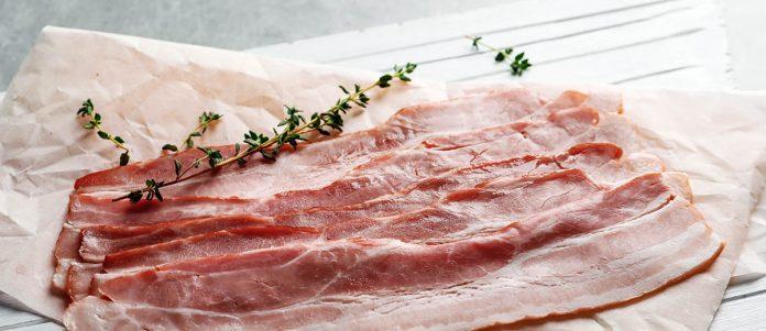 Bacon arisanal sur son papier avec une branche de thym