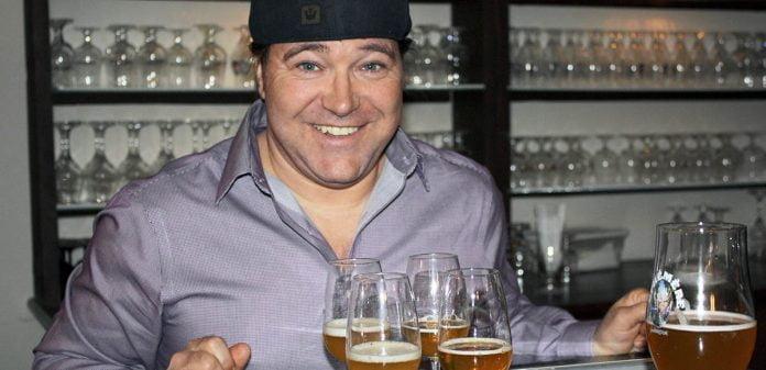 Sylvain Bouchard, le sommelier d'Unibroue, tout sourire au bar derrière quelques verres de bières