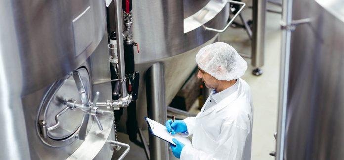 Technicien de lab en sarau blanc inspectant une cuve de brassage
