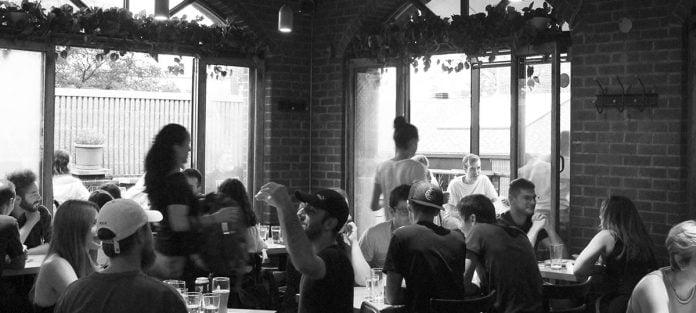 L'intérieur du Réservoir avec des clients assis aux tables et deux serveurs leur servant de la bière