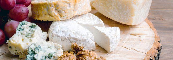 Une sélection de fromages, de noix, de jambon et de raisins sur une planche de service