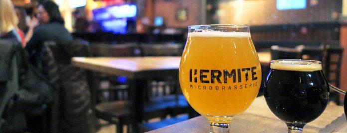 Un verre arborant fièrement le logo de la Microbrasserie L'Hermite sis sur le bar