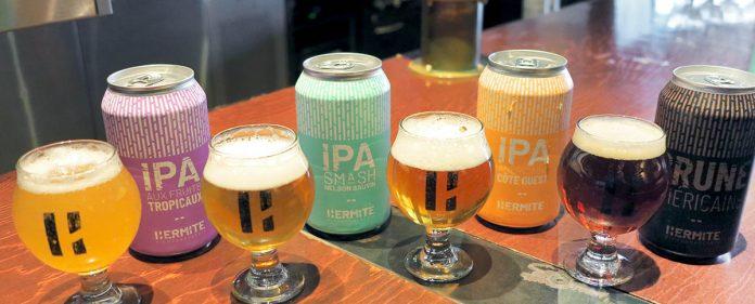 Une sélection de quatre bières de l'Ermite servie dans des verres aux côtés de leurs canettes respectives
