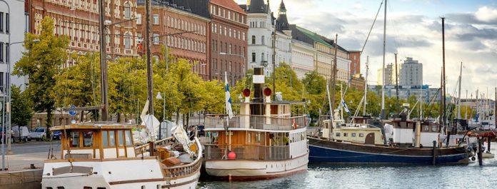 Vue d'Helsinki, capitale de la Finlande, à partir de ses berges. On y voit des péniches et des bateaux amarrés près des maisons anciennes au couché su soleil.