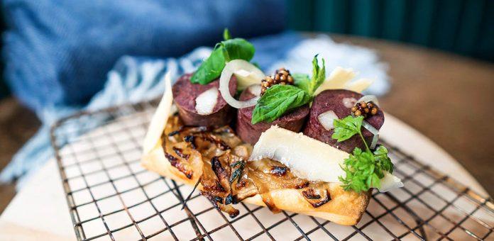 Saucisse de loup marin et lardo, pissaladière niçoise, copeaux d'Hercule 24 mois et herbes, un plat servi chez Taverne Louise bar à vin dans le cadre du Phoquefest.
