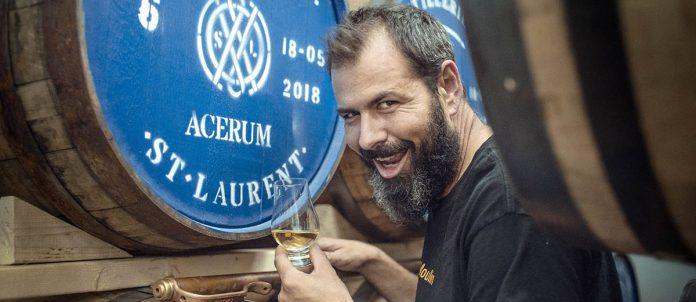 Jean-François Cloutier tout sourire devant un fût d'acerum au couleurs de la Distillerie du St Laurent