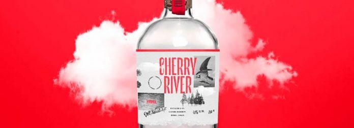 Une bouteille de gin de Cherry River devant un nuage sur un fond coloré