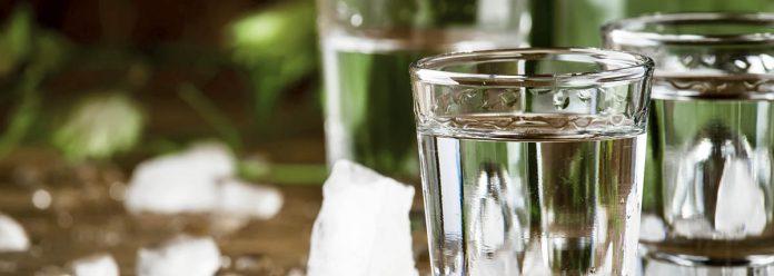 Vodka froide en verre, vieille table en bois, mise au point sélective